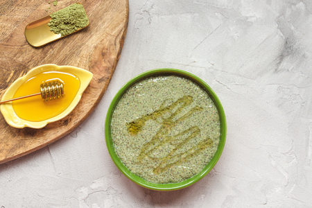 Matcha green tea chia seed pudding bowl and honey. Overhead, top view, flat lay. Superfood and vegan food concept. Wooden board and gray background, copy space.
