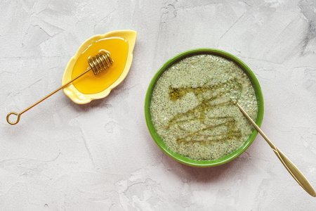 Matcha green tea chia seed pudding bowl and honey. Overhead, top view, flat lay. Superfood and vegan food concept. Gray background. 写真素材