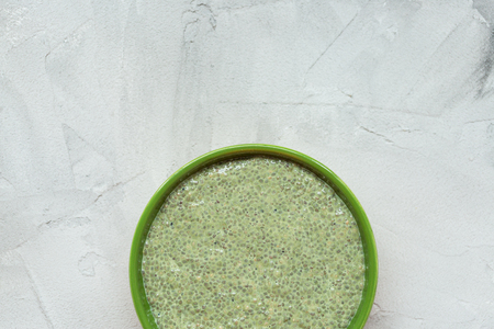 Matcha green tea chia seed pudding bowl. Close up, top view, flat lay. Superfood and vegan food concept. Gray background.