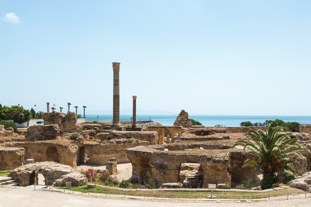 Tunis, Tunisia - May 19, 2017: Archaeological Site. Ruins of Carthage, Baths of Antoninus, columns and fragments of the walls. Sea in the background, copy space.