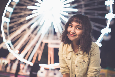 Beautiful asian girl in an amusement park at nght, smiling. Ferris wheel in the background. Copy space.