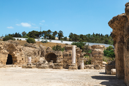 Archaeological Site. Ruins of Carthage at Baths of Antoninus, white wall arround. Tunisia.