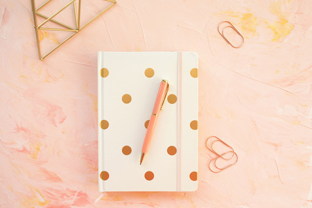 Notepad and pen on a desk workspace, pink backround. Flat lay, top view, social media hero header template, lifestyle concept.
