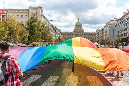 Prague, Czech Republic - August 11, 2018: People holding huge rainbow flag ot the Prague Gay Pride parade. Crowd on Wenceslas Square in front of the National Museum.