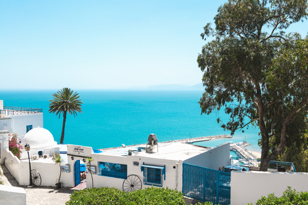 Sidi Bou Said, Tunisia - May 19, 2017: View of the street with white and blue traditional architecture, sea in the background. Blue sky, copy space. 報道画像