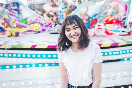 Beautiful asian girl in an amusement park, smiling. Copy space.