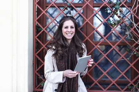 Young woman in a stylish beige trench using digital tablet computer outdoors. Spring or autumn time.