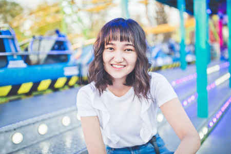 Beautiful asian girl in an amusement park, smiling. Copy space.