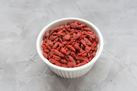 Dried goji berries in a porcelain bowl on a gray background, concept of healthy eating vegan food. Close up, selective focus, copy space. Imagens