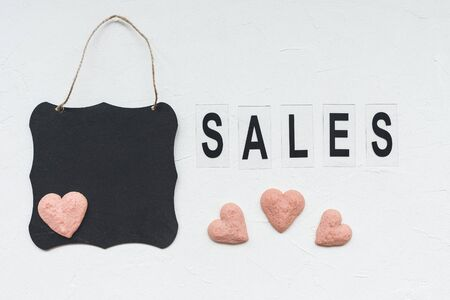 Word SALES, black board and heart shaped cookies on a white background