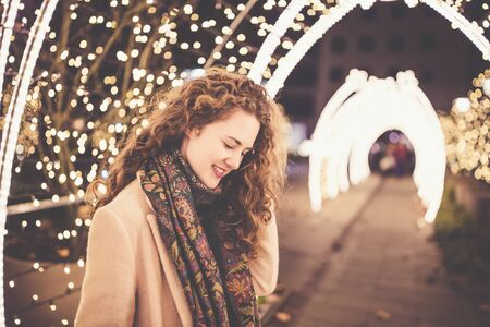 Beautiful curly hair smiling young woman in a coat outdoors with Christmas lights and decoration in the background. City street night portrait. Christmas and New Year concept