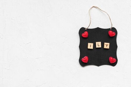 ILY leters as abbreviation of I love you and jelly hearts on a black board, white background, copy space. Top view, flat lay, mockup. Valentines Day concept Stockfoto
