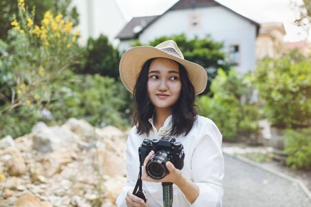 Young asian woman in white shirt and hat in a park, smiling, holding camera. Outdoor portrait.