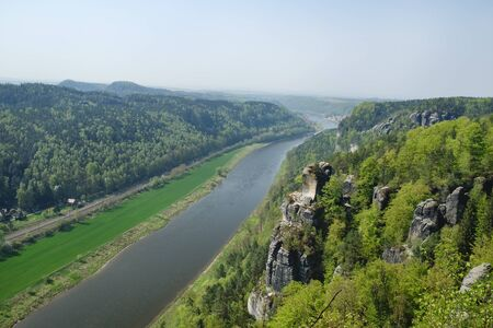 View on river Elbe from rock formations Bastei in Saxon Switzerland National Park, Germany. Blue sky, springtime.