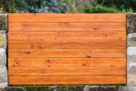 Fragment of wooden fence with horizontal planks and columns of natural stone Stock Photo