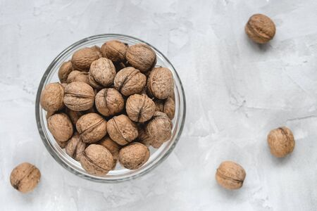 Uncracked walnuts in shell in bowl on gray background, concept of healthy eating vegan food. Close up, selective focus, copy space. Stock Photo