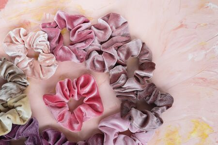 Collection of trendy velvet scrunchies on pink background. Diy accessories and hairstyles concept, copy space