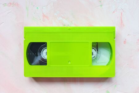 Green vintage VHS video tape on pink. Retro minimalist background, copy space