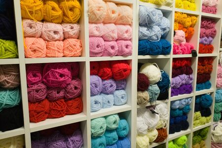Bright multicolored yarns of wool for knitting on shelves in the haberdashery shop. Knitwork handkraft concept
