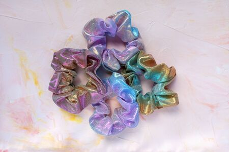 Four trendy holographic iridiscent shiny metallic scrunchies on pink background. Diy accessories and hairstyles concept, copy space