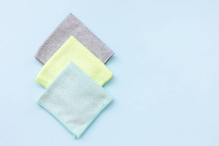 Three new folded microfiber cloth for cleaning over the blue background. Cleaning micro fabric towels for dusting and polishing. Domestic household cleaning service concept. Close up, copy space