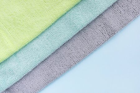 Gray, blue and yellow microfiber cloth for cleaning on blue background. Cleaning micro fabric towels for dusting and polishing. Domestic household cleaning service concept. Close up, copy space