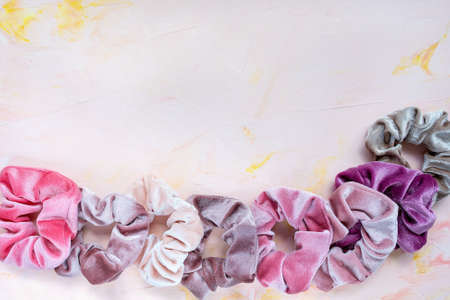Collection of trendy velvet scrunchies on pink background. Diy accessories and hairstyles concept, copy space Stockfoto