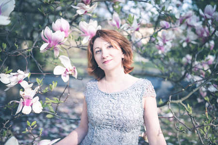 Happy middle aged Armenian woman in an elegant dress under the blooming magnolia tree. Smiling, looking at the camera. Toned, selective focus. 版權商用圖片