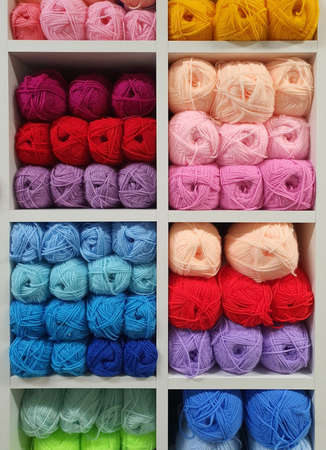 Multicolored yarns of wool for knitting on shelves in the haberdashery shop. Knitwork handkraft concept