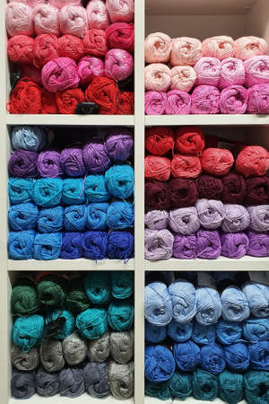 Colorful yarns of wool for knitting on shelves in the haberdashery shop. Knitwork handkraft concept Banque d'images