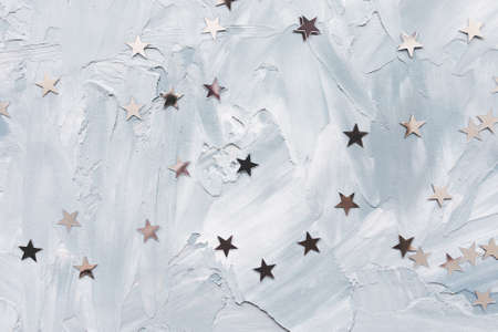 Trendy metallic foil confetti stars on white and blue light background. Winter abstract backround. Birthday party, New Year, Christmas celebration, holidays and dreams concept. Selective focus