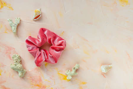 One trendy velvet scrunchie, sea shells and corals on pink backround. Flat lay, top view. Diy accessories, hairstyles, lifestyle, sea vacation and summer outfit ideas concept, copy space