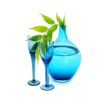 Blue vase with water, wine glasses, and a green branch