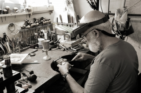 A very old jewelery shop and a jeweler handcrafting a silver dog and a cup.