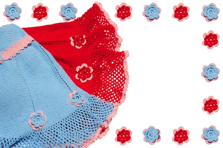 Knitted baby clothes and flowers. Red, blue and pink colors. Stock Photo