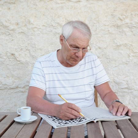 An elderly man with a cup of coffee and crossword Stock Photo
