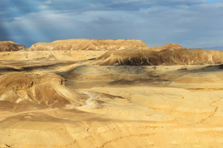 Beautiful scenery of the Israeli desert Negev. Clouds, sun and yellow mountains.