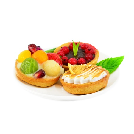 Delicious small cakes with fruit, cream and chocolate. Stock Photo