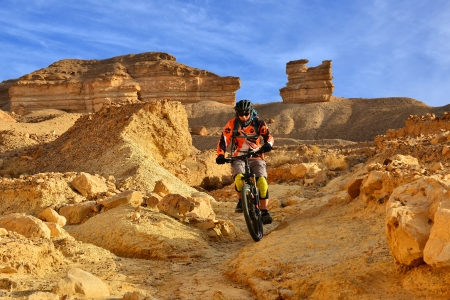 Mountain biker in a mountainous desert. Beautiful scenery and extreme sport.