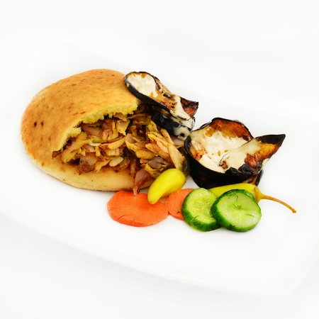Shawarma in pita with scorched eggplant in tahinni and vegetables. Stock Photo