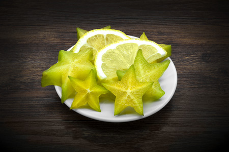 Carambola and lemon on dark brown wooden background. Stock Photo