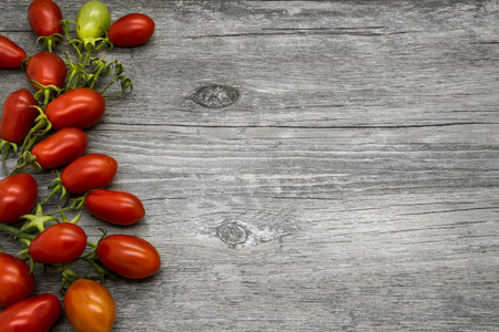 Cherry tomatoes on a gray wooden table. Vegetable border. Stock Photo