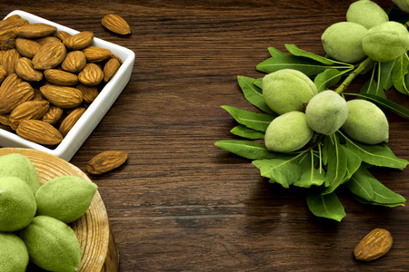 Almond branches and nuts on a wooden table.
