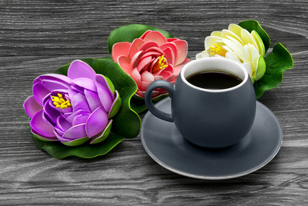 Ceramic cup of coffee and artificial water lilies on a wooden background Stock Photo