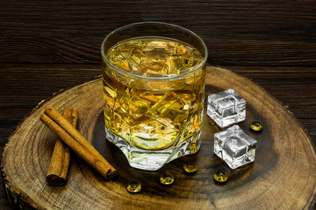 Alcoholic beverage with cinnamon and ice on a wooden background. Stock Photo
