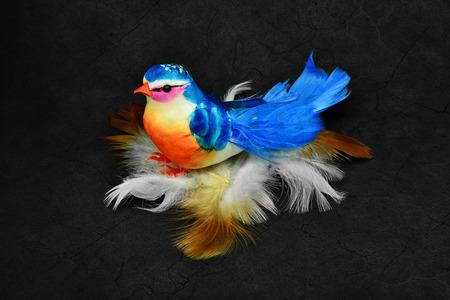 Beautiful artificial bird on natural bird feathers.