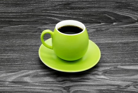 Green cup of black coffee on a wooden background.
