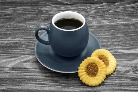 Grey ceramic cup of coffee on a wooden background.