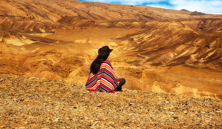 Long haired man in poncho sits in a desert. Stock Photo