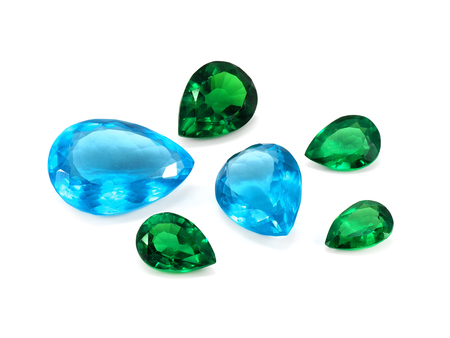 topaz: Pear shaped blue topaz and emeralds on a white background. Natural Gemstones.